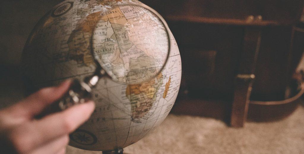 kuvituskuva: Karttapalloa tarkastellaan suurennuslasin läpi